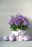 Beautiful easter eggs and spring Campanula flowers on white wooden background Royalty Free Stock Photo