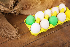 Beautiful Easter eggs in yellow carton. Beautiful yellow, green and white Easter eggs in yellow carton on old wood surface with jute decoration Royalty Free Stock Image