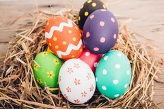 Beautiful Easter multi color egg in straw on wooden royalty free stock photo