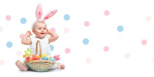 Beautiful Easter smiling little girl wearing bunny rabbit ears, with a basket full of colorful painted Easter eggs. Toddler Baby girl laughing portrait royalty free stock photo