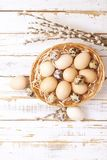 Traditional easter card template with pastel colors painted organic eggs in wicker basket with hay and decorative wildflowers. Stock Image