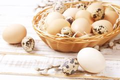 Traditional easter card template with pastel colors painted organic eggs in wicker basket with hay and decorative wildflowers. Beautiful easter table Stock Photo