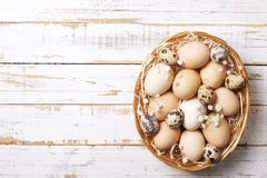 Traditional easter card template with unpainted mixed organic eggs in wicker basket with hay and decorative wildflowers. Beautiful easter table composition Royalty Free Stock Photo