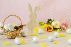 Beautiful easter table decoration with painted eggs ,rabbits and flowers in pastel colors. Simple easter decoration with eggs,feathers, bunny toy and spring royalty free stock photo