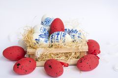 Beautiful Easter White and Red  Eggs with Blue Painted Flowers in a Nest Stock Photography