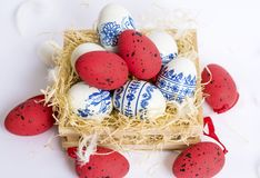 Beautiful Easter White and Red  Eggs with Blue Painted Flowers in a Nest Royalty Free Stock Photography