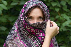 Beautiful Eastern girl in scarf. On a green background Royalty Free Stock Photo