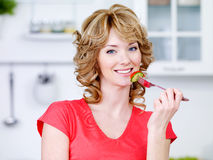 Beautiful eating woman in the kitchen Royalty Free Stock Photos