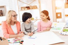 Beautiful egrandmother teaches grandchildren to draw. Children draw with paints. royalty free stock image