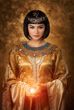 Beautiful Egyptian woman like Cleopatra with magic ball on golden background. Photo of gorgeous woman with Cleopatra makeup holding magic lighting ball Stock Photo
