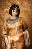 Beautiful Egyptian woman like Cleopatra with magic ball on golden background. Photo of gorgeous woman with Cleopatra makeup holding magic lighting ball royalty free stock images