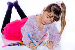 Beautiful eight year old girl drawing with color pencils Stock Image