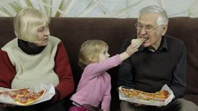 Beautiful elderly man and woman eats pizza with their granddaughter stock video footage