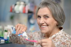 Beautiful elderly woman brushing her teeth. In the bathroom stock image