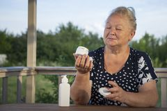 Beautiful elderly woman doing make-up outdoors at home veranda royalty free stock photos