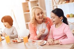 Beautiful elderly woman is feeding sausages to little granddaughter in kitchen at dinner table. Beautiful elderly women is feeding sausages to little Stock Photo