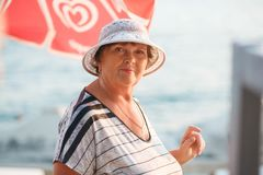 Beautiful elderly woman in a hat on a beach. Beautiful elderly woman hve rest on a beach. Portrait of elederly woman of 65 years in glasses and hat Stock Image