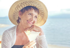 Beautiful elderly woman in a hat with a cocktail in hand. Summer Stock Image