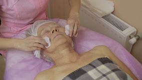 Beautiful elderly woman having face cleaning stock video