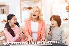 Beautiful elderly woman plays on keyboard with grandchildren who sing into microphone. royalty free stock images