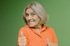 Beautiful elderly woman. Portrait of a beautiful older woman on a green background Stock Image
