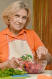 Beautiful elderly woman. Portrait of a beautiful elderly woman preparing dinner Royalty Free Stock Image