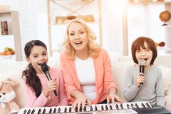 Beautiful elderly woman plays on keyboard with grandchildren who sing into microphone. royalty free stock image