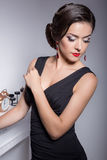 Beautiful elegant attractive sexy girl in evening dress with hairstyle and bright makeup is evening voila the fireplace, posing in Stock Photo