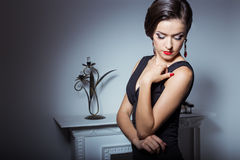 Beautiful elegant attractive sexy girl in evening dress with hairstyle and bright makeup is evening voila the fireplace, posing in Stock Image