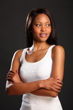 Beautiful elegant black woman in white vest. Portrait of elegant, beautiful black woman looking away in a quiet moment, arms folded, wearing white vest Royalty Free Stock Image
