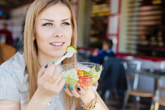 Beautiful elegant blond young woman eating salad in restaurant portrait image Royalty Free Stock Photography