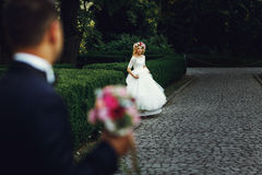 Beautiful elegant blonde bride running towards charming groom outdoors in park royalty free stock photos