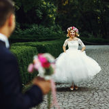 Beautiful elegant blonde bride running towards charming groom outdoors in park royalty free stock photo