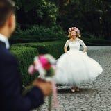 Beautiful elegant blonde bride running towards charming groom ou Royalty Free Stock Photo
