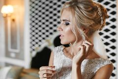 Beautiful and elegant blonde model girl with bright make-up and stylish wedding hairstyle, in lace white dress adjusting stock images