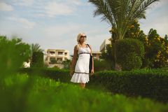 Beautiful and elegant blonde model girl, in white dress and sunglasses, posing outdoors royalty free stock photography