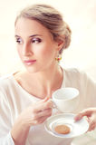 Beautiful elegant blonde sitting in a cafe drinking tea Stock Photos