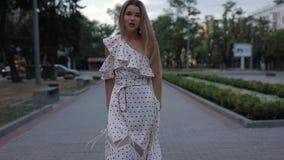 Beautiful elegant woman in dress walking at summer city alley, slowmotion. Beautiful elegant blonde woman in dress walking at summer city alley, slowmotion stock footage