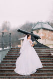 Beautiful elegant bride in long luxurious white dress posing on stairs with old cannon at background Royalty Free Stock Photo