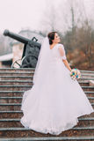 Beautiful elegant bride in long luxurious white dress posing on stairs outdoors with old cannon at background Stock Image