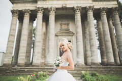 Beautiful elegant bride with perfect wedding dress and bouquet posing near old castle Stock Image