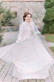 Beautiful elegant bride posing on green park paved road waving her gorgeous wedding dress Royalty Free Stock Images
