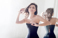 Beautiful elegant brunette in a corset. Girl and its reflexion Royalty Free Stock Photography