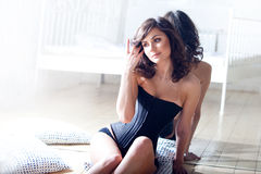 Beautiful elegant brunette in a corset. Girl and its reflexion Royalty Free Stock Photo