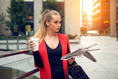 Beautiful elegant business woman walking to the city office with a coffee, newspaper and smiling outdoor. Portrait of beautiful elegant business woman walking to Stock Photography