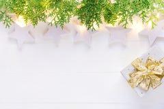 Beautiful elegant Christmas New Year background. White stars sparkling golden lights garland green juniper gift box on plank wood stock photo