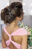 Beautiful elegant evening hairstyle on dark hair beautiful girl with an ornament from stones in her hair, hairstyle for the weddin Stock Image