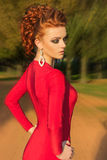 Beautiful elegant girl with beautiful makeup and hair in a red evening dress in the Park Royalty Free Stock Image
