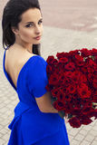 Beautiful elegant girl with a bouquet of red roses. Fashion portrait of beautiful elegant lady with black hair with bouquet of red roses royalty free stock photography