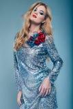 Beautiful elegant girl in brilliant paillettes dress. Portrait of beautiful elegant woman in brilliant fashionable paillettes dress on blue background in studio Stock Photo